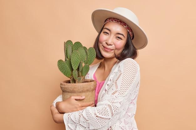 Portret van jonge aziatische vrouw omarmt ingemaakte cactus