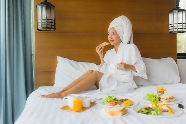 Portret van jonge aziatische vrouw op bed met ontbijt