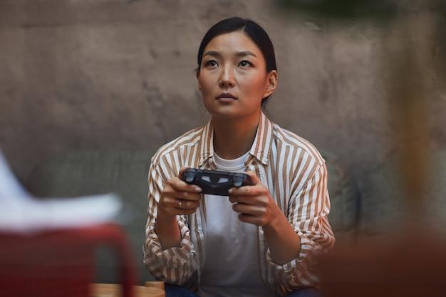 Portret van jonge aziatische vrouw videogames spelen via gaming console
