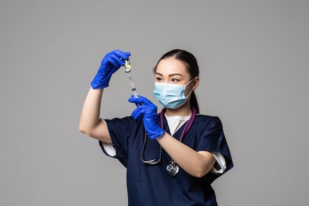 Portret van jonge aziatische vrouwelijke arts die covid-19-vaccin uit vaccinfles trekt