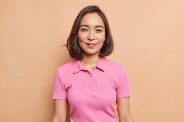 Portret van jonge aziatische vrouwelijke model met natuurlijke schoonheid donker haar rouge wangen gezonde huid kijkt gelukkig naar voren draagt casual roze t-shirt geïsoleerd over beige muur