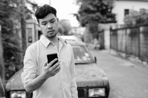 Portret van jonge aziatische zakenman die mobiele telefoon met behulp van tegen roestige oude auto in de straten buiten