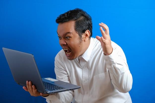 Portret van jonge aziatische zakenman die op laptop typt, gekke boze uitdrukking, over blauwe muurachtergrond met exemplaarruimte