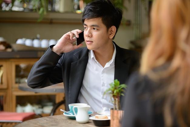 Portret van jonge aziatische zakenman en jonge aziatische onderneemster die samen bij de koffiewinkel ontspannen