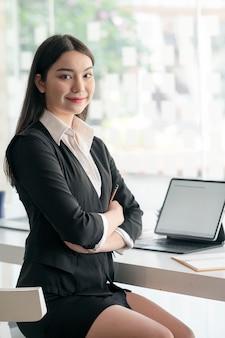 Portret van jonge aziatische zakenvrouw zitten met gekruiste armen, glimlachend en camera kijken.