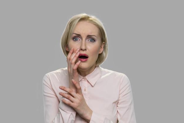 Portret van jonge bange blonde vrouw. geschokt bang vrouw hand in hand in de buurt van gezicht. gelaatsuitdrukking van angst.