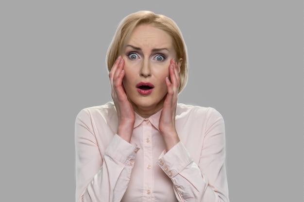 Portret van jonge bange vrouw. verbaasd bang blanke vrouw hand in hand in de buurt van gezicht. vrouw van middelbare leeftijd die geschokt nieuws krijgt.