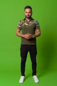 Portret van jonge bebaarde indiase man op groen