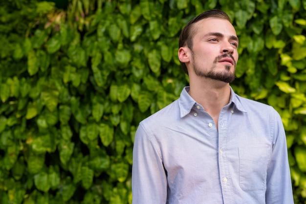 Portret van jonge bebaarde modieuze man buitenshuis