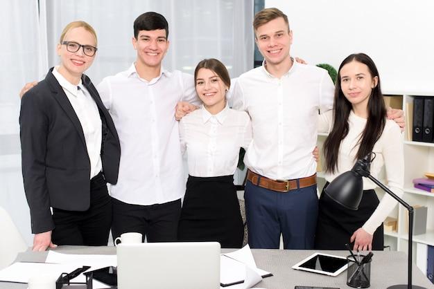 Portret van jonge bedrijfsmensen met hun wapens rond elkaar schouders in het bureau