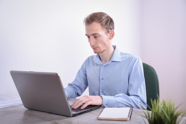 Portret van jonge bedrijfsmensenzitting bij zijn laptop van de bureaudesktop in het bureau internet marketing, financiën, bedrijfsconcept