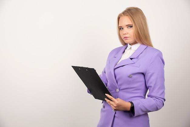 Portret van jonge bedrijfsvrouw die en klembord bevindt zich houdt.