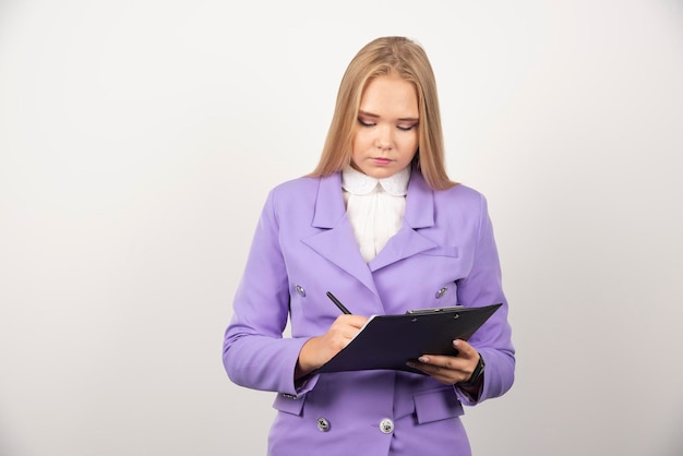 Portret van jonge bedrijfsvrouw die en op klembord bevindt zich kijkt. hoge kwaliteit foto