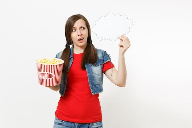 Portret van jonge bezorgde vrouw in casual kleding kijken naar film film bedrijf zeggen wolk met plaats voor tekst, copyspace en emmer popcorn geïsoleerd op een witte achtergrond. emoties in bioscoopconcept