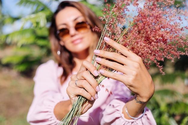 Portret van jonge blanke gelooide vrouw in romantische roze jurk ronde oorbellen zilveren armband en zonnebril met wilde bloemen
