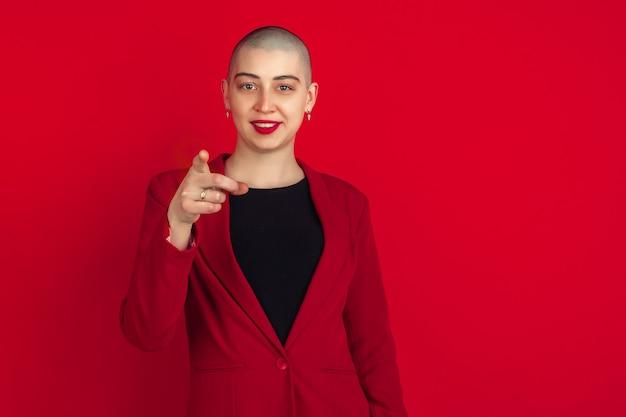 Portret van jonge blanke kale vrouw op rode muur