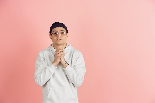 Portret van jonge blanke man met heldere emoties op roze studio achtergrond