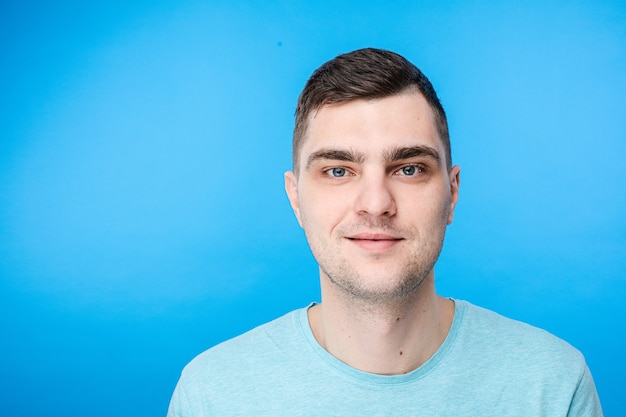 Portret van jonge blanke man met kort donker haar en mooi gezicht is blij