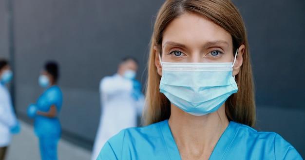 Portret van jonge blanke mooie vrouw arts in medisch masker camera kijken. close up van vrouwelijke arts in ademhalingsbescherming. multi-etnische artsencollega's op achtergrond.