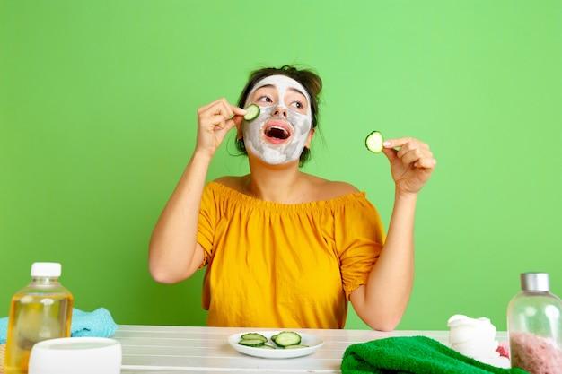 Portret van jonge blanke vrouw in haar schoonheidsdag, huid en haarverzorgingsroutine. vrouwelijk model met natuurlijke cosmetica gezichtsmasker voor make-up toe te passen. lichaams- en gezichtsverzorging, natuurlijk schoonheidsconcept.