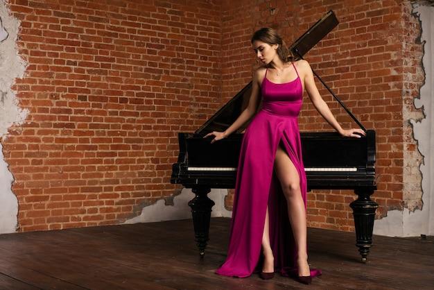 Portret van jonge blanke vrouw in pluizige jurk staande in de buurt van piano