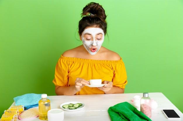 Portret van jonge blanke vrouw in schoonheidsdag, huid en haarverzorgingsroutine. vrouwelijk model koffie, thee drinken tijdens het toepassen van gezichtsmasker. verbaasd. selfcare, natuurlijke schoonheid en cosmetica concept.