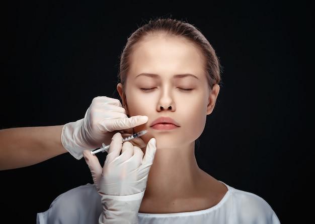 Portret van jonge blanke vrouw krijgt cosmetische injectie