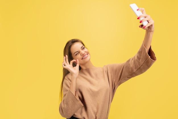 Portret van jonge blanke vrouw met heldere emoties geïsoleerd op gele studio achtergrond