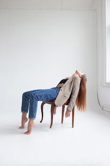 Portret van jonge blanke vrouw met lang haar in zwarte top, blauwe spijkerbroek en colbert, liggend op een stoel in de studio met haar kin omhoog, haar hoofd achterover gooien. mooie dame die zich voordeed op witte achtergrond