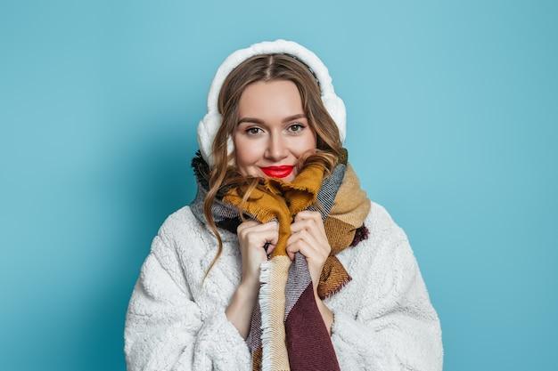 Portret van jonge blanke vrouw met rode lippen in witte kunstmatige eco bontjas geïsoleerd op blauwe muur. winter seizoen.