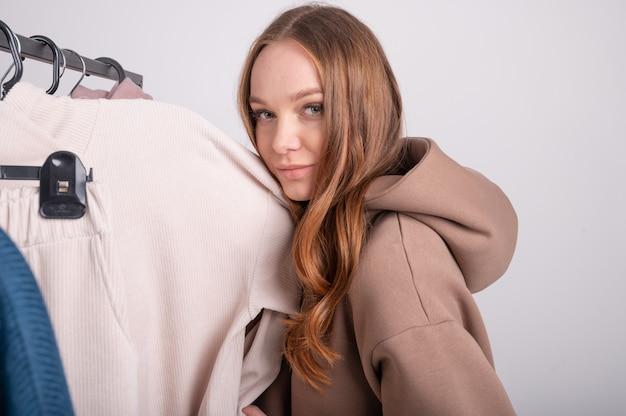 Portret van jonge blanke vrouw roodharige meisje in de winkel onderzoekt en kiest kleding close-up