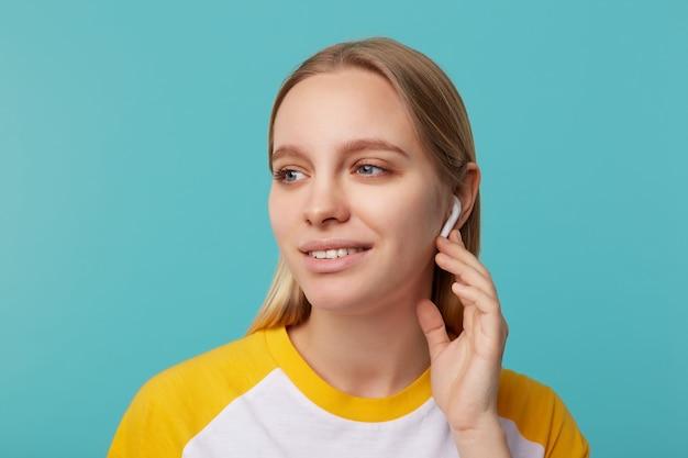 Portret van jonge blauwogige blonde langharige dame met koptelefoon die bedachtzaam opzij kijkt en zachtjes glimlacht, geïsoleerd op blauw