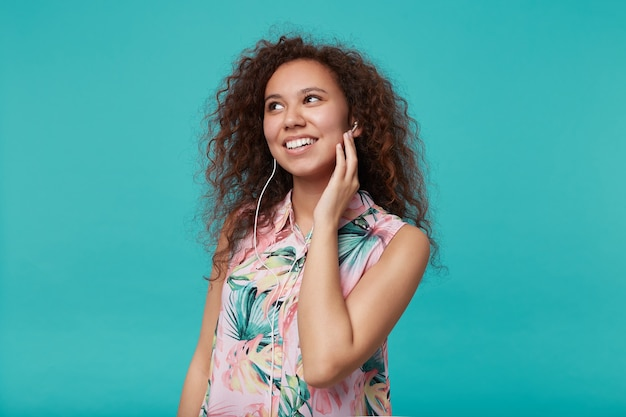 Portret van jonge blij bruinharige gekrulde vrouw die positief glimlachte en hand ophief naar haar oor tijdens het luisteren naar muziek, geïsoleerd op blauw