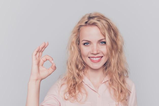 Portret van jonge blonde glimlachende vrouw die ok-teken op grijs toont
