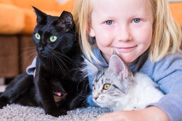 Portret van jonge blonde kinderen met zijn twee katachtige katten thuis