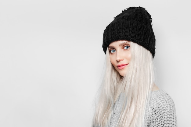 Portret van jonge blonde leuke vrouw die zwarte hoed draagt.