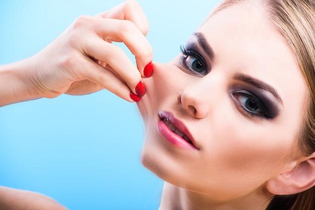 Portret van jonge blonde model in studio op blauwe achtergrond