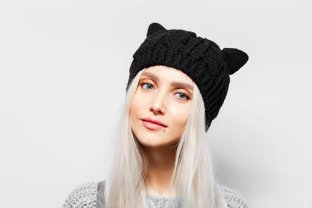 Portret van jonge blonde mooie vrouw die zwarte hoed met kattenoren draagt.