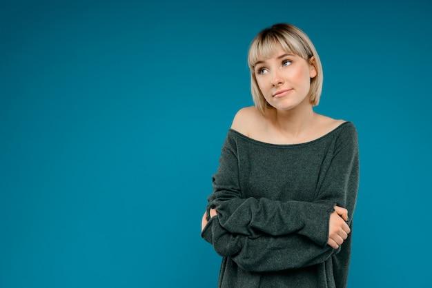 Portret van jonge blonde mooie vrouw over blauw muurexemplaar