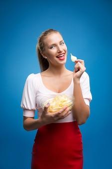 Portret van jonge blonde vrouw die chips eet en een glaskom houdt