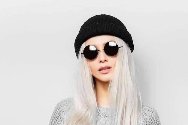 Portret van jonge blonde vrouw die ronde zonnebril en zwarte beanie hoed draagt.