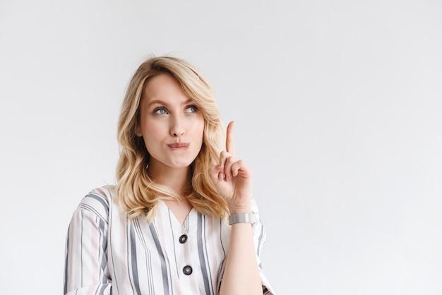 Portret van jonge blonde vrouw die vrijetijdskleding draagt die copyspace bekijkt en vinger omhoog richt die over witte muur wordt geïsoleerd
