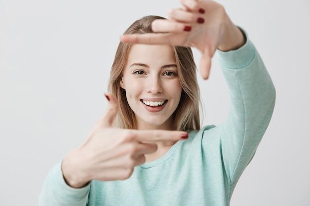 Portret van jonge blonde vrouw frame gebaar met handen maken