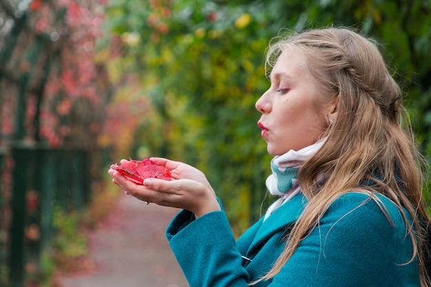 Portret van jonge blonde vrouw houdt rode bladeren in haar handen en blaast ze weg.
