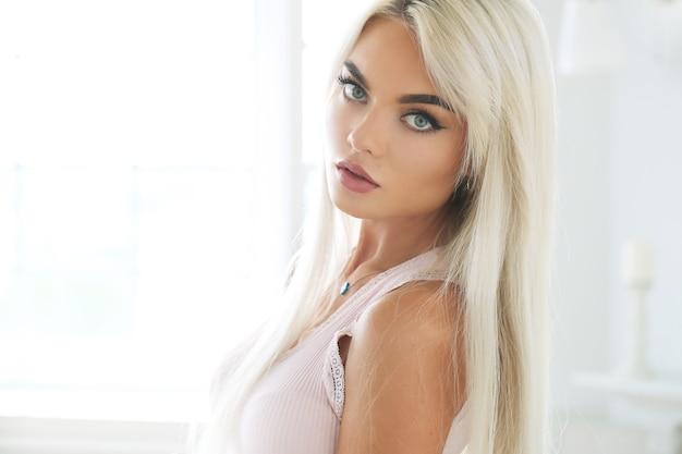 Portret van jonge blonde vrouw met gebruinde huid en manierkleding