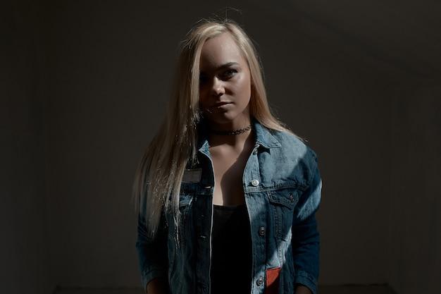 Portret van jonge blonde vrouw op donkere muur
