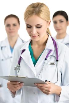 Portret van jonge blonde vrouwelijke arts omringd door medisch team, bestand met documenten kijken. gezondheidszorg en geneeskunde concept.