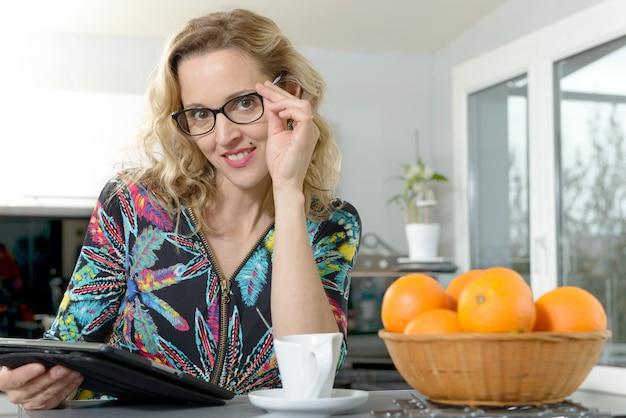 Portret van jonge blondevrouw in de keuken met tabletcomputer