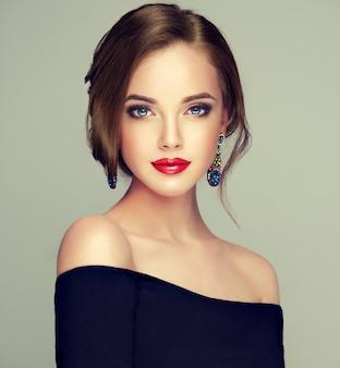 Portret van jonge, bruinharige mooie vrouw met lang, goed verzorgd haar verzameld in elegante avondkapsel. kapperskunst, haarverzorging, make-up en schoonheidsproducten.