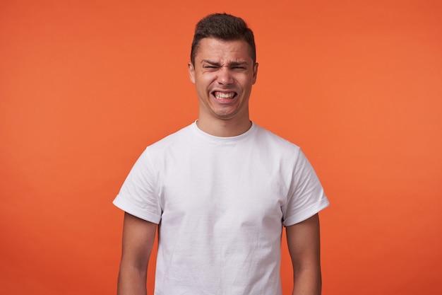 Portret van jonge brunette man met kort kapsel grimassen zijn gezicht en tanden tonen terwijl kijken naar camera, staande over oranje achtergrond met handen naar beneden
